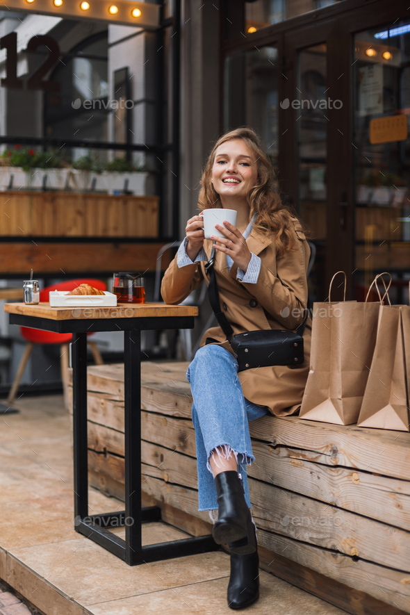 Young cheerful woman in trench coat and jeans happily looking in - Stock Photo - Images