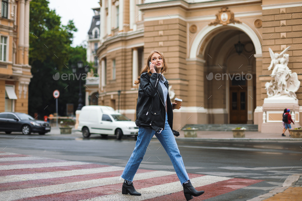 Young beautiful woman in leather jacket and jeans holding cup of - Stock Photo - Images