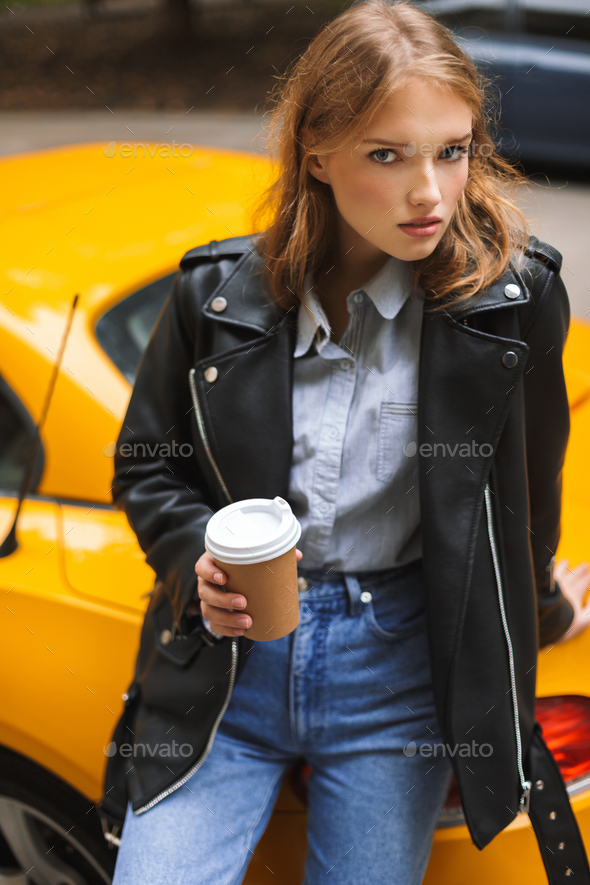 Young beautiful woman in leather jacket leaning on yellow sport - Stock Photo - Images