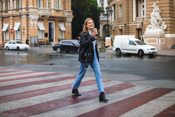 Young smiling woman in leather jacket and jeans joyfully looking - Stock Photo - Images