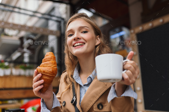 Portrait of beautiful smiling girl in trench coat happily lookin - Stock Photo - Images