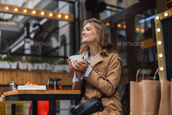 Young attractive woman in trench coat happily looking aside whil - Stock Photo - Images