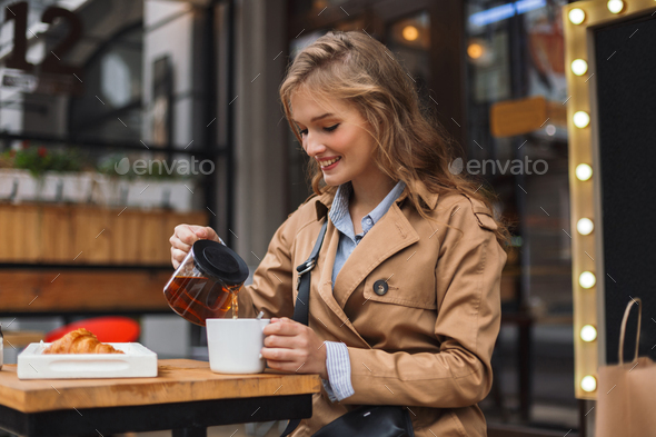Young woman in trench coat happily holding teapot and white cup - Stock Photo - Images