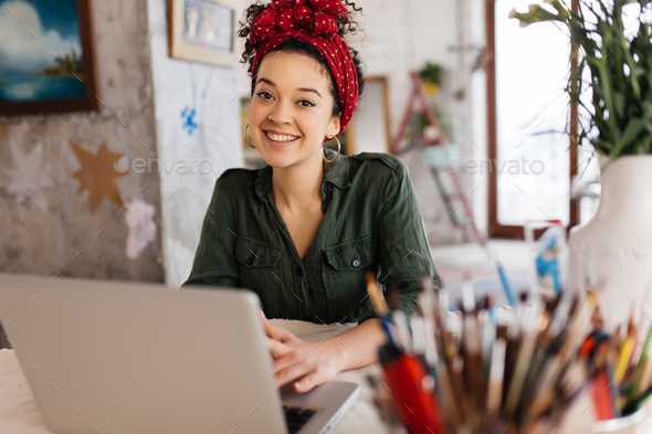 Young attractive woman with dark curly hair sitting at the table - Stock Photo - Images