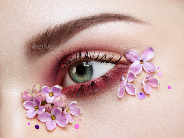 Eye makeup woman with a lilac flowers - Stock Photo - Images