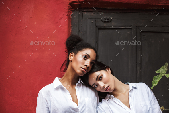 Young beautiful women in white shirts thoughtfully looking aside - Stock Photo - Images