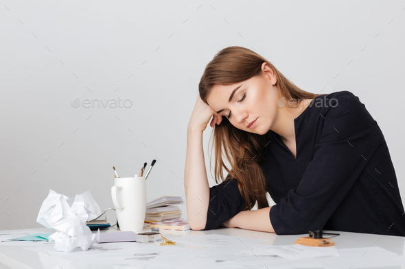 Photo of cute lady sitting at the white desk and sleeping while leaning head on her hand isolated - Stock Photo - Images