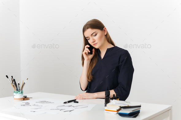 Portrait of young pretty lady sitting at the white desk and talking on her cellphone - Stock Photo - Images