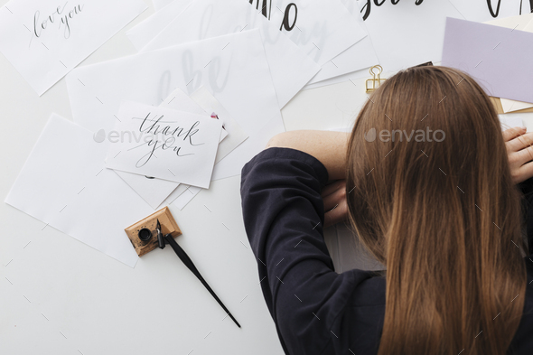 Photo of tired lady sitting and sleeping while leaning head on her hands at the white desk  - Stock Photo - Images