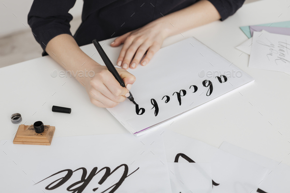 Close up photo of young woman hands writing alphabet on paper on desk  isolated - Stock Photo - Images