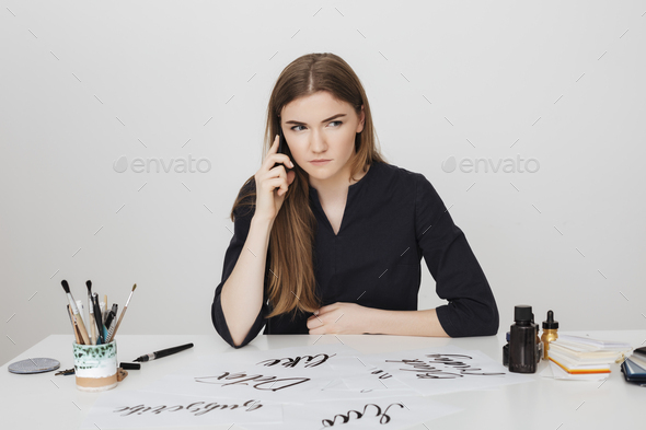 Lady sitting at the white desk and talking on her cellphone while seriously looking aside - Stock Photo - Images