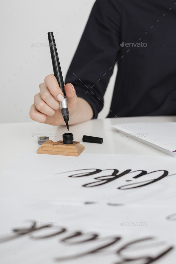 Close up photo of young woman hand writing on paper on desk  isolated - Stock Photo - Images
