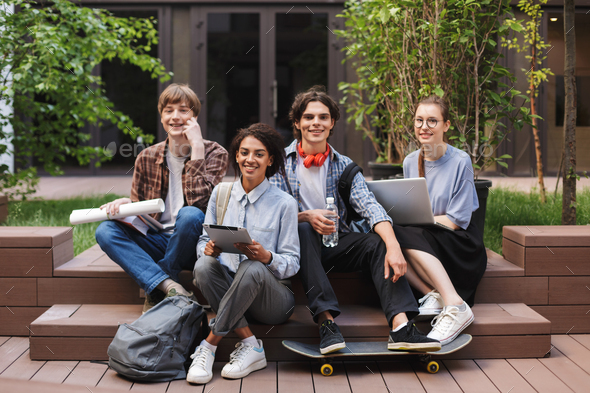 Group of cool smiling students sitting and happily looking in camera while spending time together  - Stock Photo - Images