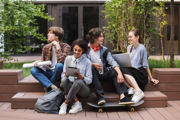 Photo of young joyful students sitting and doing what they want - Stock Photo - Images
