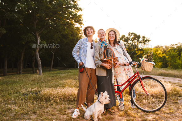 Beautiful girls with bicycle and wood basket in hands joyfully l - Stock Photo - Images