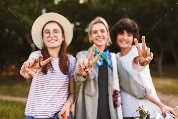 Close up smiling girls happily showing victory gestures and look - Stock Photo - Images