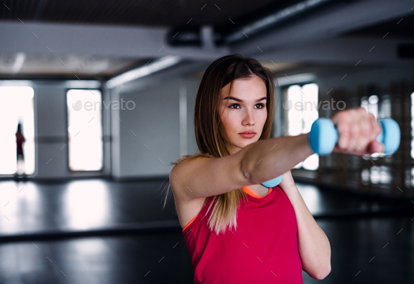 A Portrait Of Young Girl Or Woman Doing Exercise With Dumbbells In A Gym
