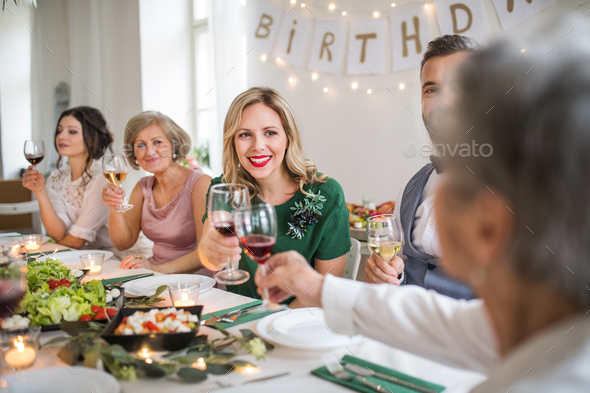 A big family sitting at a table on a indoor birthday party, clinking glasses. - Stock Photo - Images