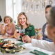 A big family sitting at a table on a indoor birthday party, clinking glasses. - PhotoDune Item for Sale