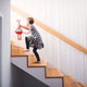 A small child with a soft toy walking up the stairs. - PhotoDune Item for Sale