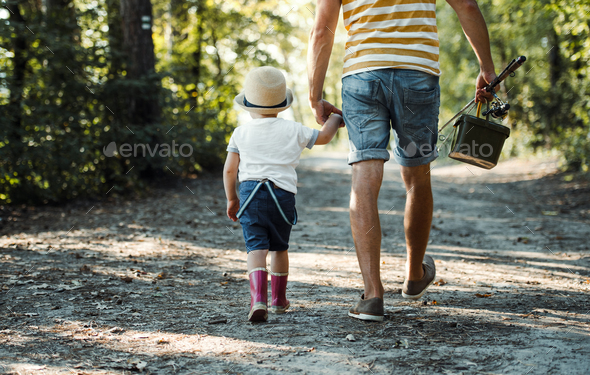 A rear view of father with a small toddler son going fishing. - Stock Photo - Images