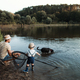A mature father with a small toddler son and dog outdoors fishing by a lake. - PhotoDune Item for Sale