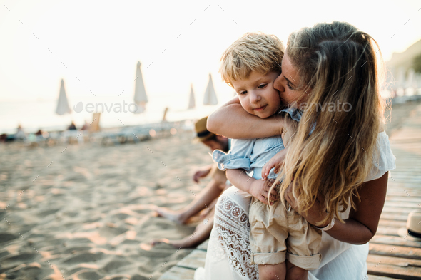Young mother with a toddler boy having fun on beach on summer holiday. - Stock Photo - Images