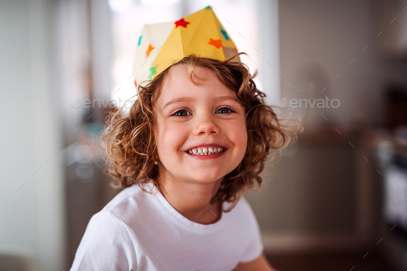 A small girl with a paper crown at home, looking at camera. - Stock Photo - Images