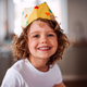 A small girl with a paper crown at home, looking at camera. - PhotoDune Item for Sale