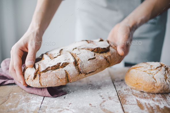Baker or chef holding fresh made bread - Stock Photo - Images