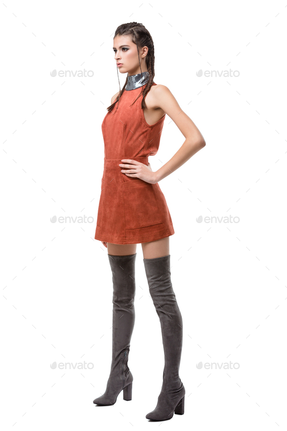 Young lady standing and dreamely looking aside in light brown dress and knee high boots - Stock Photo - Images