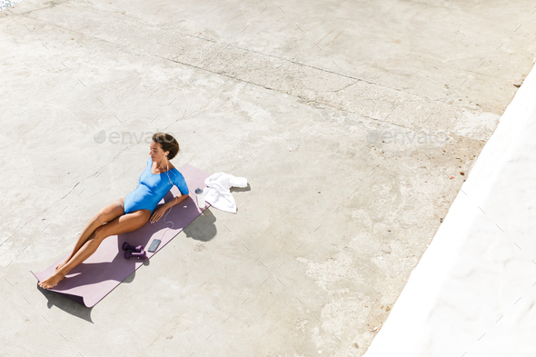 Beautiful woman with brown short hair in blue swimsuit lying on purple yoga mat - Stock Photo - Images