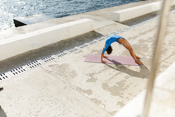 Woman With Dark Short Hair In Blue Swimsuit Doing Yoga While
