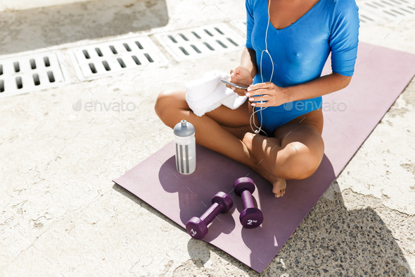 Woman body in blue swimsuit sitting on yoga mat in lotus pose with cellphone in hands - Stock Photo - Images
