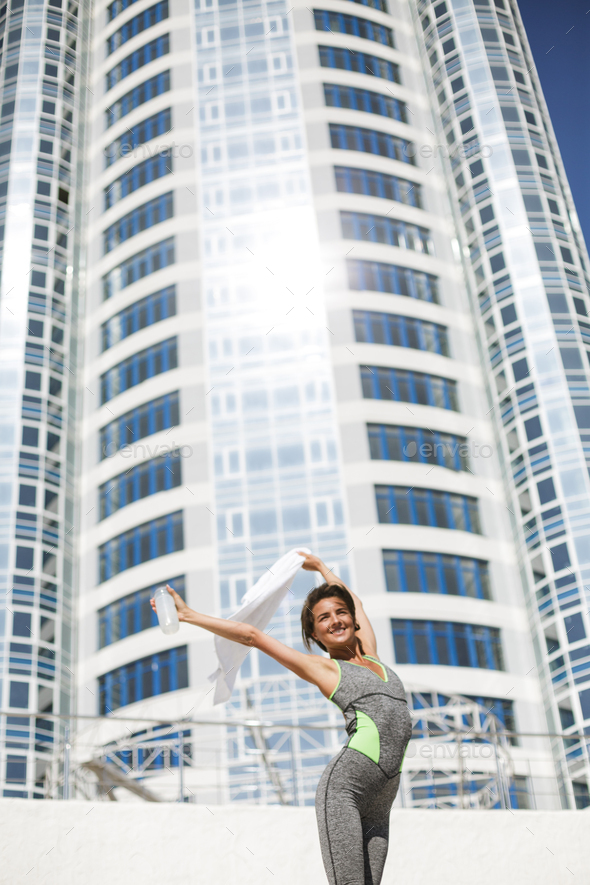 Happy woman in modern sport suit standing and raising her hands up holding towel and bottle of water - Stock Photo - Images
