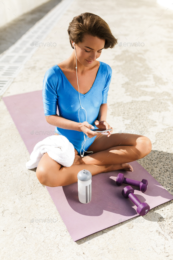 Woman with dark short hair in blue swimsuit sitting on yoga mat and listening music on her cellphone - Stock Photo - Images