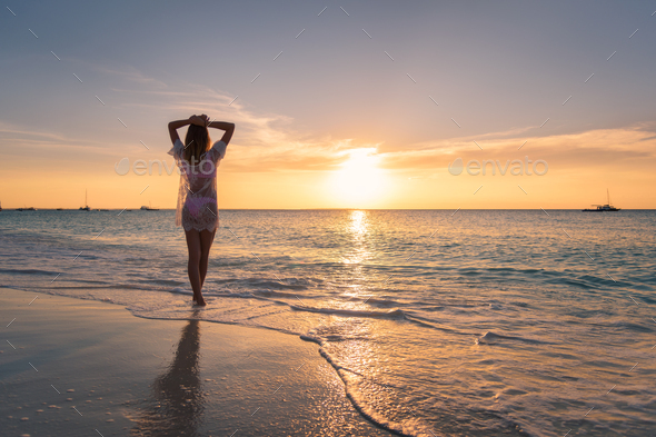 Beautiful young woman on the sandy beach at sunset - Stock Photo - Images