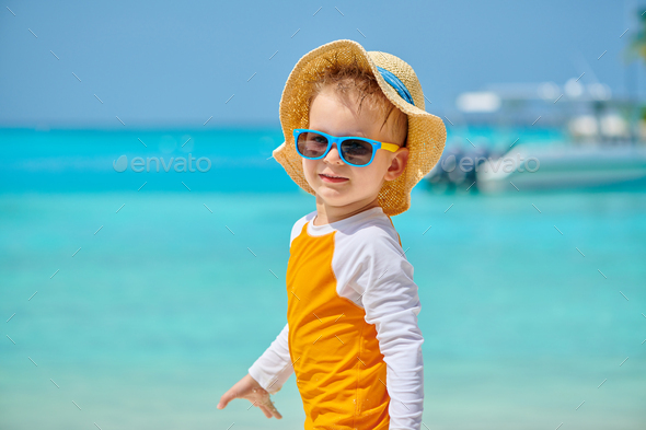 Toddler boy with sunglasses on beach - Stock Photo - Images