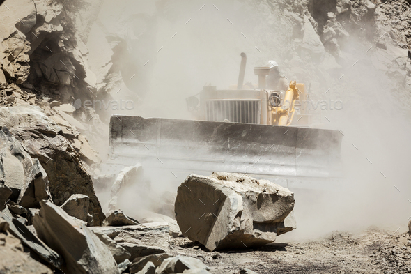 Bulldozer cleaning landslide on road in Himalayas - Stock Photo - Images