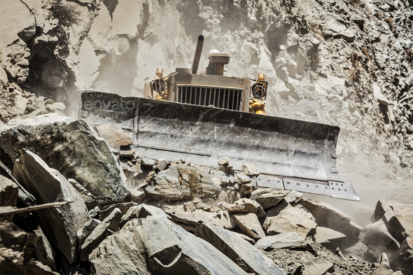 Bulldozer doing road construction in Himalayas - Stock Photo - Images