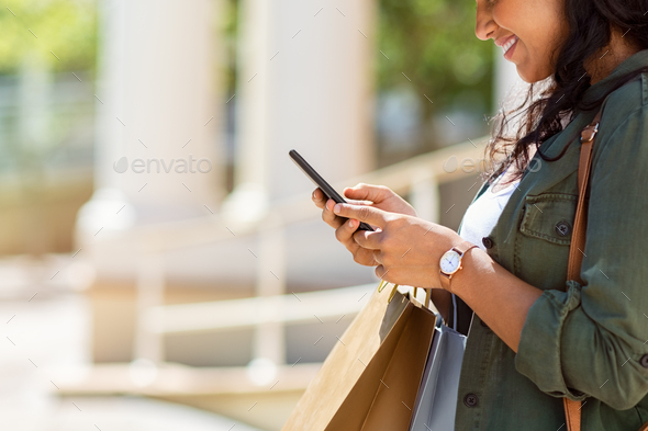 Woman with shopping bags using phone - Stock Photo - Images