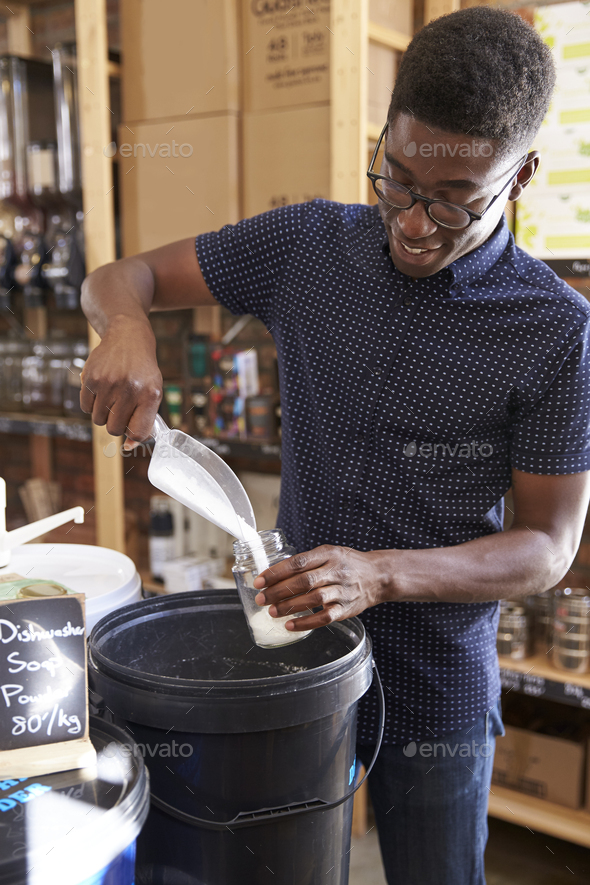 Man Filling Container With Dishwasher Powder In Plastic Free Grocery Store - Stock Photo - Images