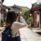 Young woman traveler walking and photographing at lijiang old town in Yunnan province, China - PhotoDune Item for Sale