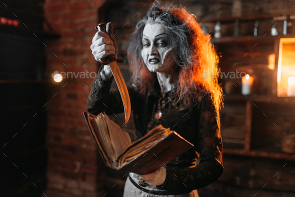 Scary witch holds spellbook and knife - Stock Photo - Images
