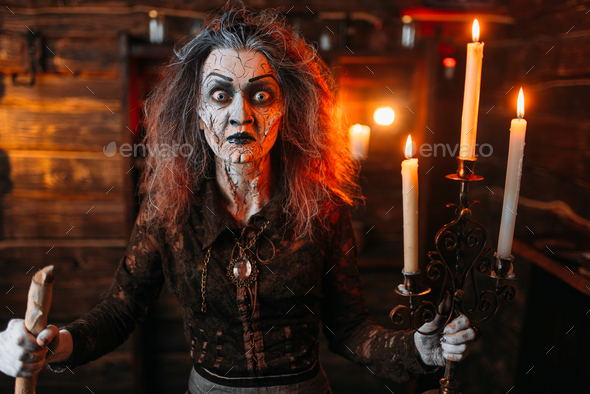 Scary witch with candlestick and cane reads spell - Stock Photo - Images