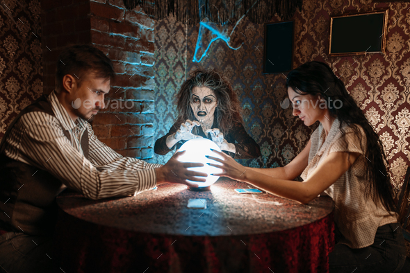 Foreteller calls the spirits over a crystal ball - Stock Photo - Images