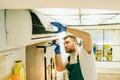 Repairman in uniform cleans the air conditioner - PhotoDune Item for Sale