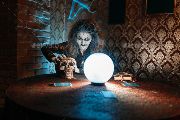 Scary witch with human skull over a crystal ball - Stock Photo - Images