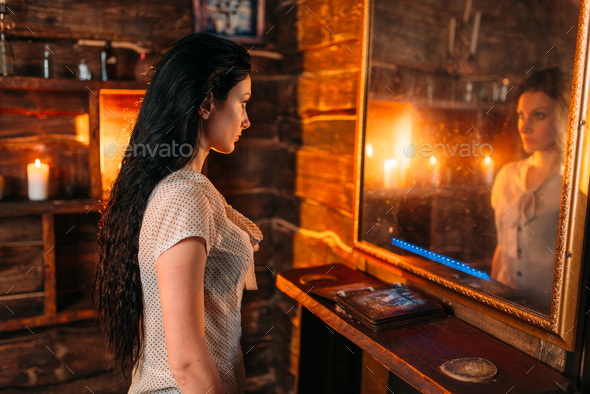 Young woman at the mirror on spiritual seance - Stock Photo - Images