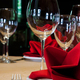 Table in a restaurant with a tablecloth, red napkins, wine glasses and cutlery. - PhotoDune Item for Sale